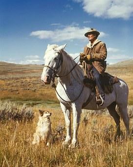 Dog sitting beside Rancher on horseback, out on the range